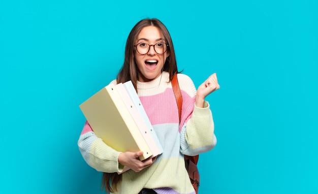 Młoda ładna kobieta czuje się zszokowana, podekscytowana i szczęśliwa, śmieje się i świętuje sukces, mówiąc wow!