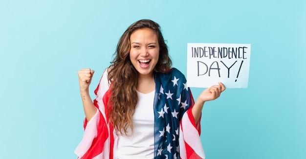 Młoda ładna kobieta czuje się zszokowana, śmieje się i świętuje koncepcję dnia niepodległości sukcesu