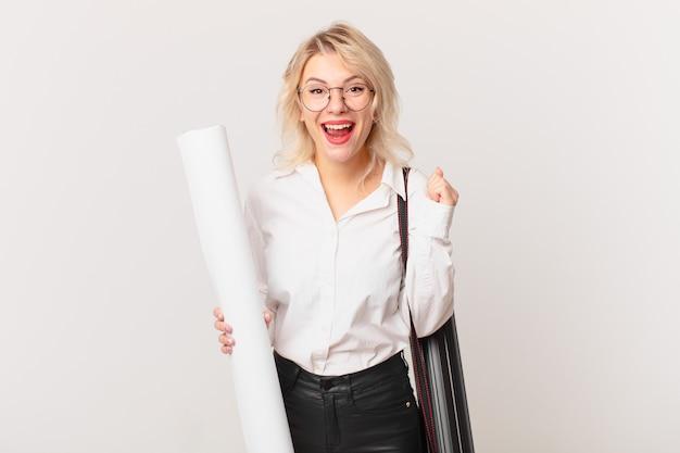 Młoda ładna kobieta czuje się zszokowana, śmieje się i świętuje sukces. koncepcja architekta