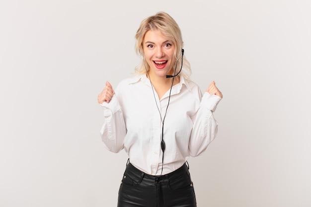Młoda ładna kobieta czuje się zszokowana, śmieje się i świętuje sukces. koncepcja telemarketingu