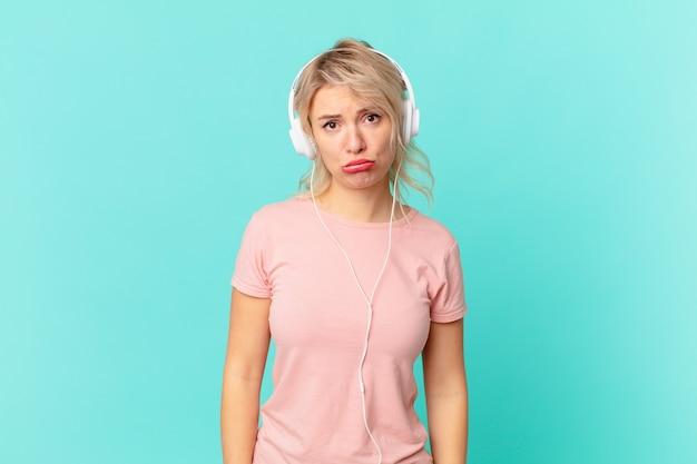 Młoda ładna kobieta czuje smutek i płacz z nieszczęśliwym spojrzeniem i płaczem. koncepcja muzyki do słuchania