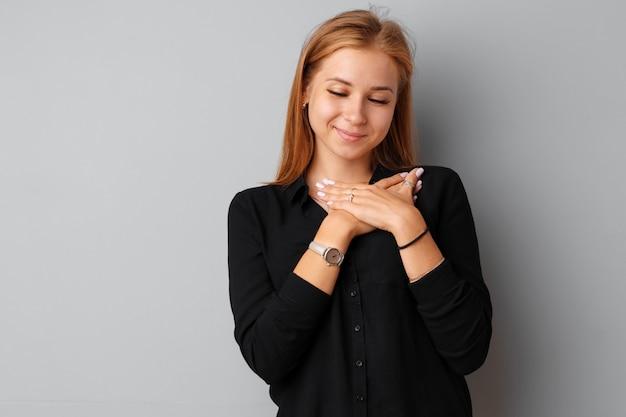 Młoda ładna kobieta dotyka jej serce z jej rękami nad szarym tłem