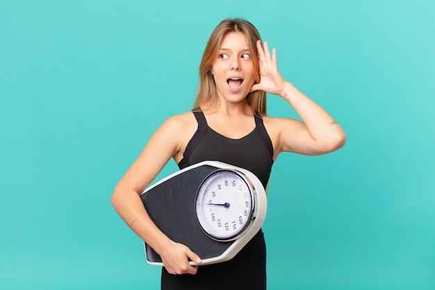 Młoda ładna kobieta fitness czuje się szczęśliwa, podekscytowana i zaskoczona