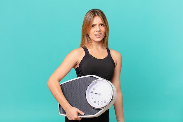 Młoda ładna kobieta fitness czuje się zdziwiona i zdezorientowana