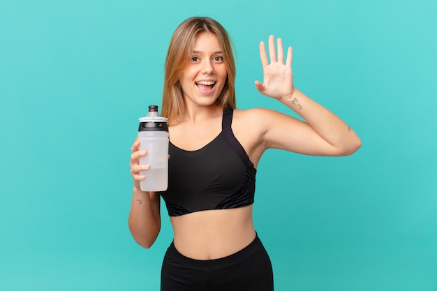 Młoda ładna kobieta fitness uśmiecha się radośnie, macha ręką, wita cię i wita