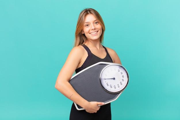 Młoda ładna kobieta fitness uśmiecha się szczęśliwie z ręką na biodrze i pewnie