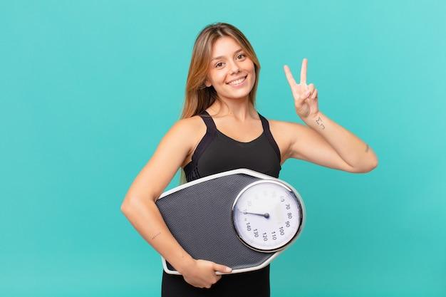 Młoda ładna kobieta fitness uśmiechnięta i wyglądająca przyjaźnie, pokazująca numer dwa