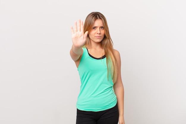 Młoda ładna kobieta fitness wygląda poważnie pokazując otwartą dłoń, wykonując gest zatrzymania