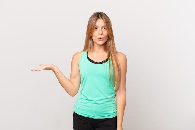 Młoda ładna kobieta fitness wyglądająca na zaskoczoną i zszokowaną, z opuszczoną szczęką trzymającą przedmiot