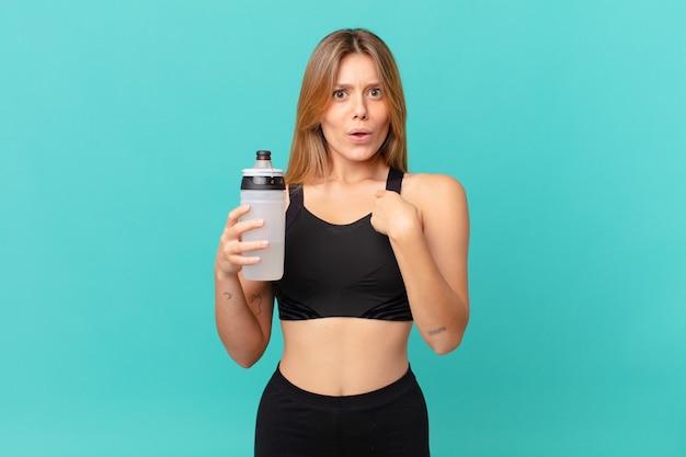 Młoda ładna kobieta fitness wyglądająca na zszokowaną i zaskoczoną z szeroko otwartymi ustami, wskazując na siebie