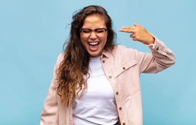 Młoda ładna kobieta gestykuluje na niebieskiej ścianie