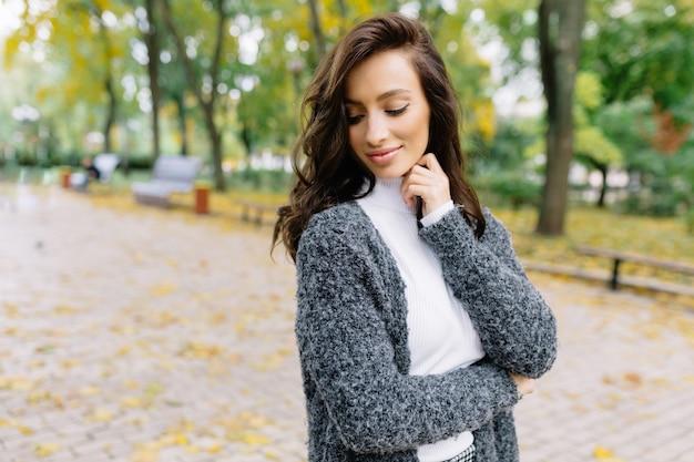 Młoda ładna kobieta idzie po parku i uśmiecha się z zamkniętymi oczami. ma ciemne, krótkie włosy i cudowne, duże niebieskie oczy.