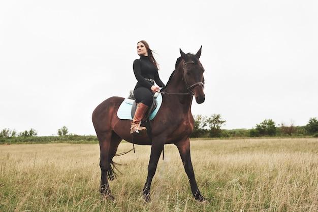 Młoda ładna kobieta - jazda konna, sport jeździecki w okresie wiosennym