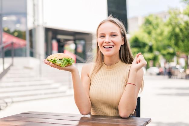 Młoda ładna kobieta je burgera na świeżym powietrzu na ulicy