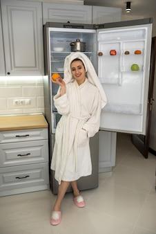 Młoda ładna kobieta jedzenie owoców w kuchni, koncepcja diety. zdrowa żywność dla każdego