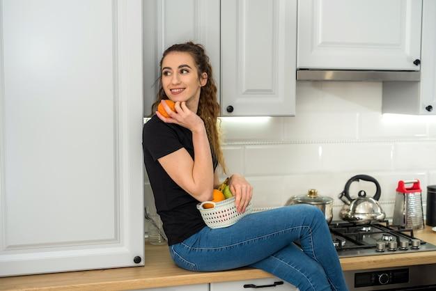 Młoda ładna kobieta jedzenie owoców w kuchni