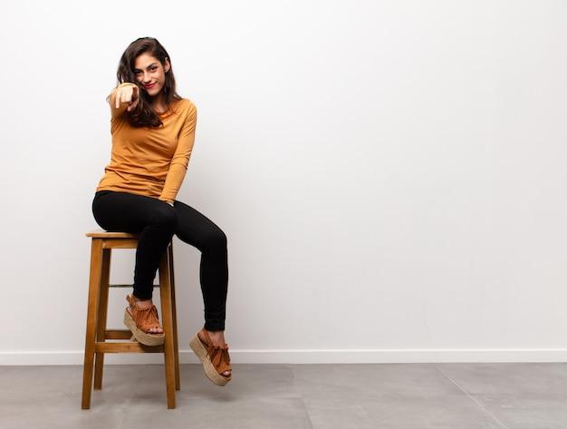 Młoda ładna kobieta jest usytuowanym na stołku