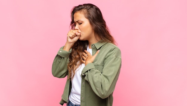 Młoda ładna kobieta kaszel na różowym tle