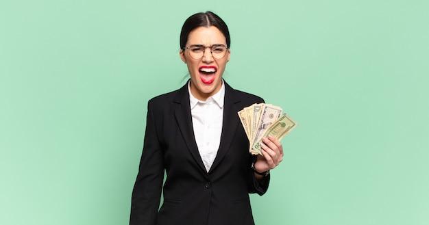 """Młoda ładna kobieta krzycząca agresywnie, wyglądająca na bardzo złą, sfrustrowaną, oburzoną lub zirytowaną, krzyczącą """"nie"""". koncepcja biznesu i banknotów"""