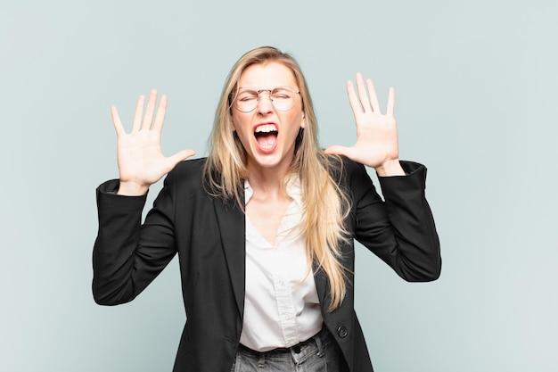 Młoda ładna kobieta krzycząca w panice lub złości, zszokowana, przerażona lub wściekła, z rękami przy głowie