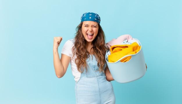 Młoda ładna kobieta krzyczy agresywnie z gniewnym wyrazem twarzy i trzyma kosz na pranie