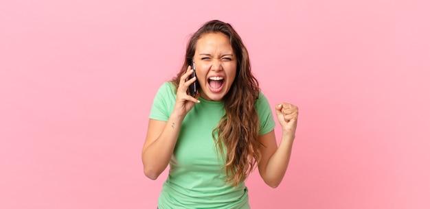 Młoda ładna kobieta krzyczy agresywnie z gniewnym wyrazem twarzy i trzyma smartfona