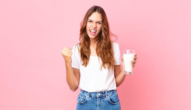 Młoda ładna kobieta krzyczy agresywnie z gniewnym wyrazem twarzy i trzyma szklankę mleka