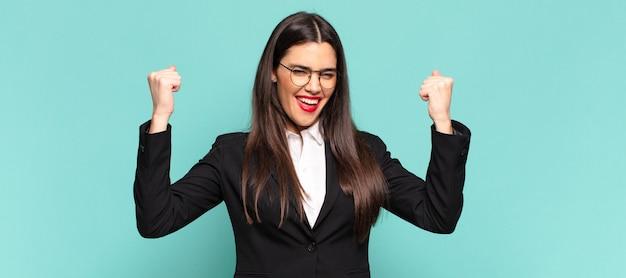 Młoda ładna kobieta krzyczy agresywnie z gniewnym wyrazem twarzy lub z zaciśniętymi pięściami świętuje sukces. pomysł na biznes