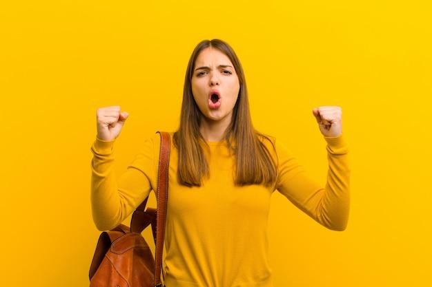 Młoda ładna kobieta krzyczy agresywnie z gniewnym wyrazem twarzy lub zaciśniętymi pięściami, świętując sukces przeciwko pomarańczowi