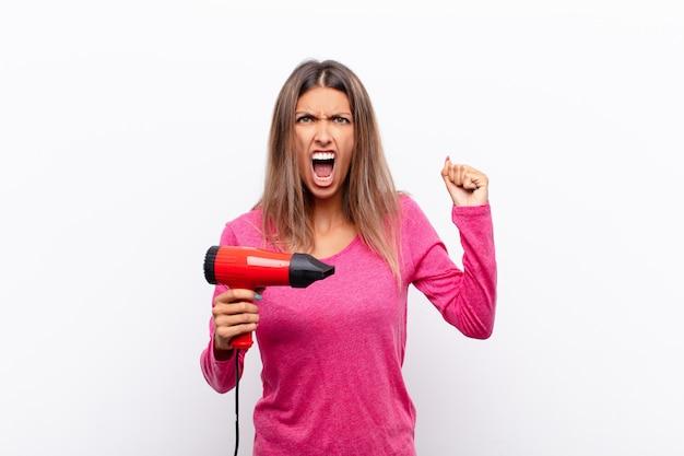 Młoda ładna kobieta krzyczy agresywnie z gniewnym wyrazem twarzy lub zaciśniętymi pięściami, świętując sukces suszarką do włosów.