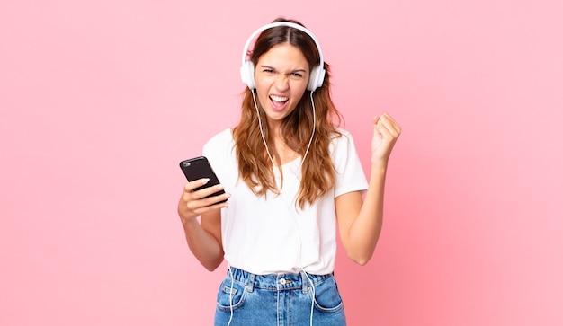 Młoda ładna kobieta krzyczy agresywnie ze złym wyrazem twarzy ze słuchawkami i smartfonem