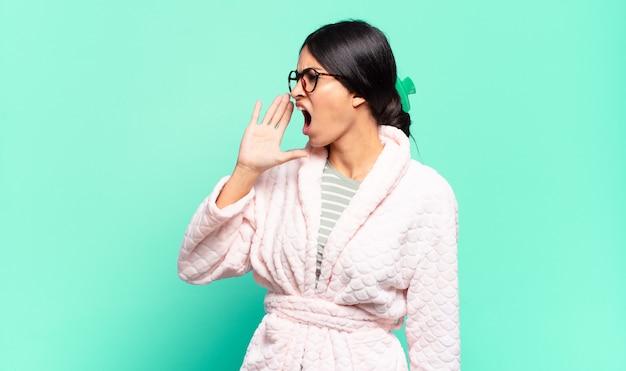 Młoda ładna kobieta krzyczy głośno i ze złością, aby skopiować miejsce z boku, z ręką przy ustach. koncepcja piżamy