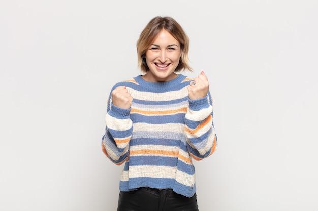 Młoda ładna kobieta krzyczy triumfalnie, śmiejąc się i czując radość i podekscytowanie podczas świętowania sukcesu