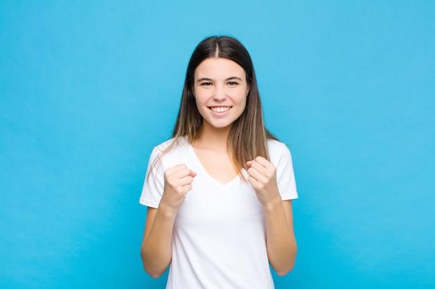 Młoda ładna kobieta krzyczy triumfalnie, śmiejąc się i czując się szczęśliwa i podekscytowana, świętując sukces przy niebieskiej ścianie