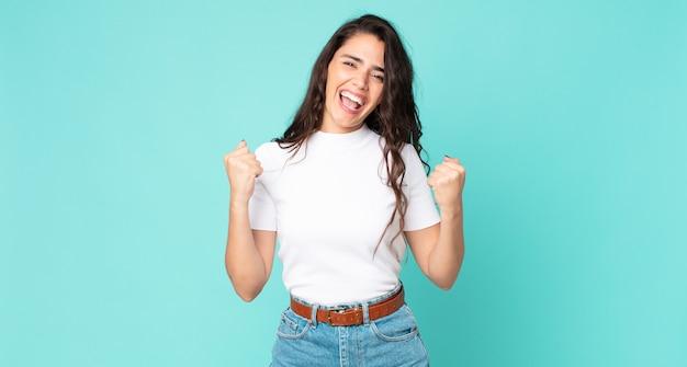 Młoda ładna kobieta krzyczy triumfalnie, śmieje się i czuje się szczęśliwa i podekscytowana podczas świętowania sukcesu
