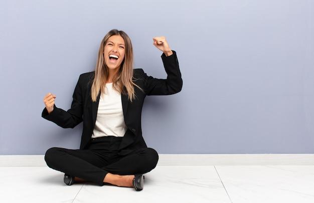 Młoda ładna kobieta krzyczy triumfalnie, wyglądając jak podekscytowany, szczęśliwy i zaskoczony zwycięzca, świętuje koncepcję biznesową