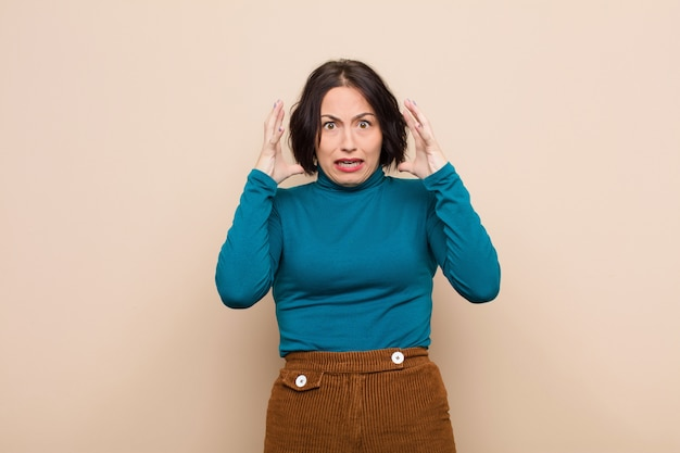 Młoda ładna kobieta krzyczy z rękami w powietrzu, czuje się wściekła, sfrustrowana, zestresowana i zdenerwowana beżową ścianą