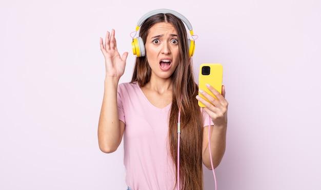 Młoda ładna kobieta krzyczy z rękami w powietrzu. słuchawki i smartfon