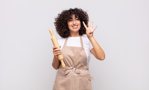 Młoda ładna kobieta kucharz uśmiecha się i wygląda przyjaźnie, pokazując numer cztery lub czwarty z ręką do przodu, odliczając w dół