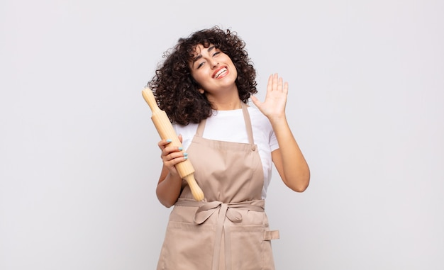 Młoda ładna kobieta kucharz uśmiecha się radośnie i wesoło, macha ręką, wita i wita lub żegna się