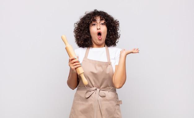 Młoda ładna kobieta kucharz wygląda na zaskoczoną i zszokowaną, z opuszczoną szczęką, trzymająca przedmiot z otwartą dłonią z boku
