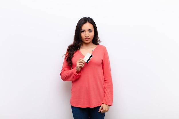 Młoda ładna kobieta łacińskiej na płaskiej ścianie z kartą kredytową