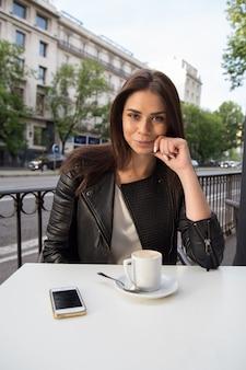 Młoda ładna kobieta ma kawę na tarasie na ulicie.