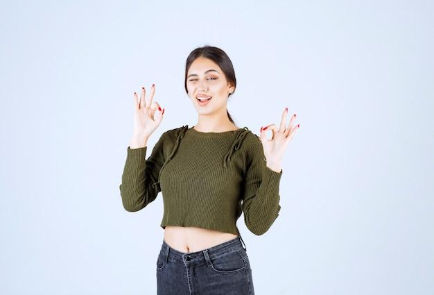 Młoda ładna kobieta modelka mruga i pokazuje ok gesty.