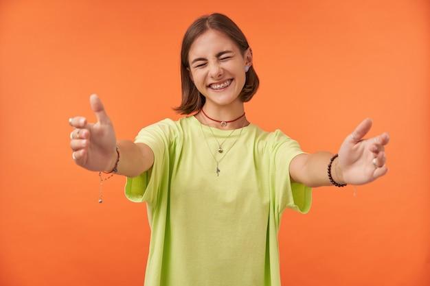 Młoda ładna kobieta mruży oczy, uśmiechając się i wyciągając rękę do uścisku. studentka szczęśliwa, że widzi swoich przyjaciół. ubrana w zieloną koszulkę, szelki, bransoletki, naszyjnik. portret na pomarańczowej ścianie