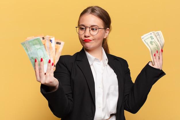 Młoda ładna kobieta myli koncepcję pieniędzy wyrażenie