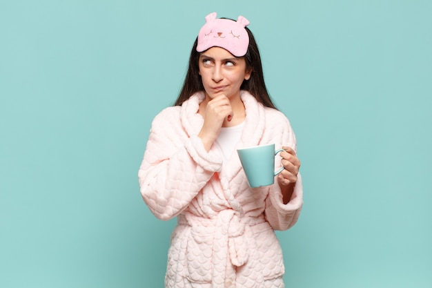 Młoda, ładna kobieta myśląca, wątpiąca i zdezorientowana, mająca różne opcje, zastanawiająca się, którą decyzję podjąć. budząc się w koncepcji piżamy