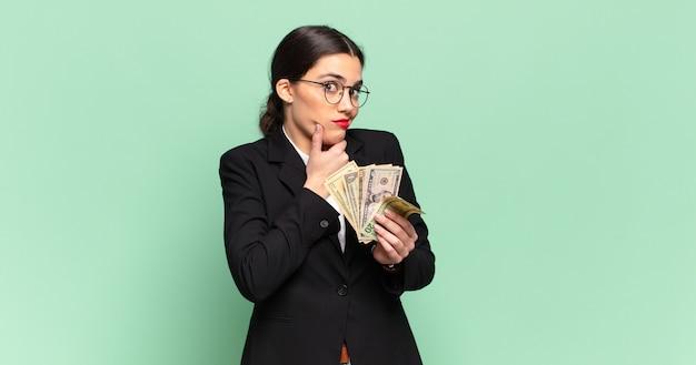 Młoda, ładna kobieta myśląca, wątpiąca i zdezorientowana, mająca różne opcje, zastanawiająca się, którą decyzję podjąć. koncepcja biznesu i banknotów