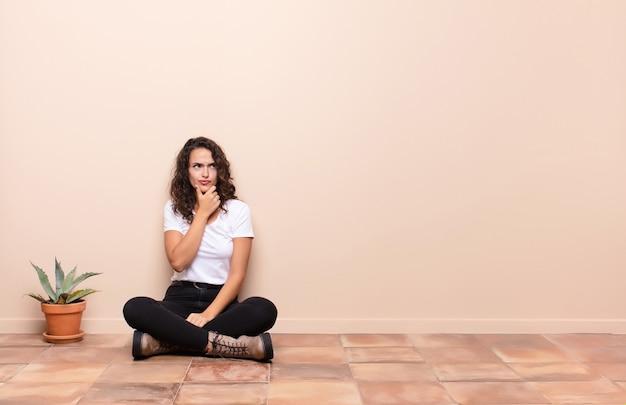 Młoda ładna kobieta myśli, czując się niepewnie i zdezorientowana, z różnymi opcjami, zastanawiając się, jaką decyzję podjąć siedząc na tarasie