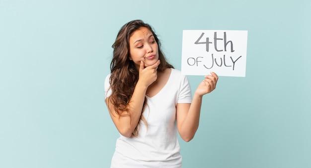 Młoda ładna kobieta myśli, czuje się wątpiąca i zdezorientowana koncepcja dnia niepodległości